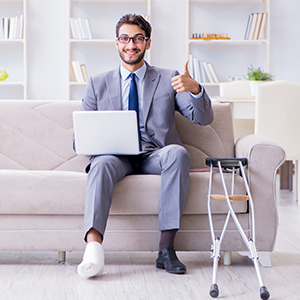 man with foot injury using laptop on couch encino ca